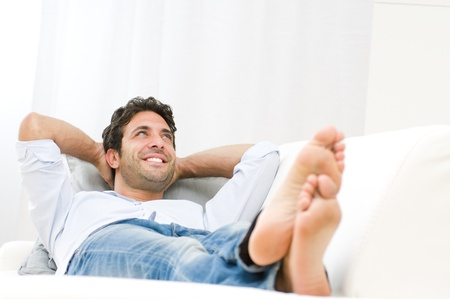 Smiling young man relaxing and dreaming on sofa at home photo