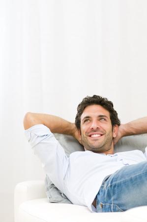spokojený: Usmívající se mladý muž sní při své budoucnosti a při odpočinku na pohovce doma