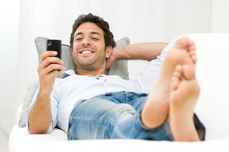 net surfing: Giovane uomo sorridente navigare in rete e di messaggistica di testo con il cellulare in casa Archivio Fotografico