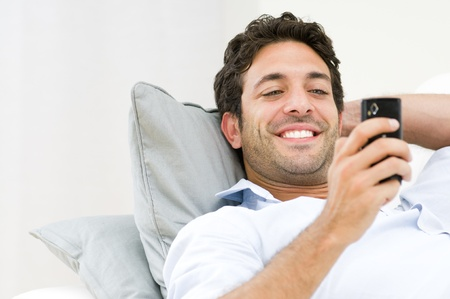 Beautiful young man relaxing on sofa and looking at his smart phone  photo
