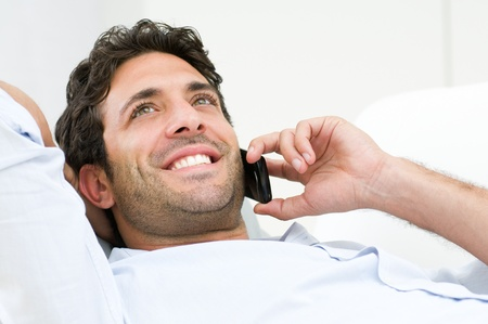 Happy smiling man talking on mobile while relaxing at home photo