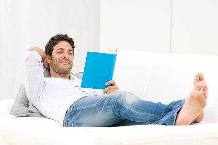 mann couch: L�chelnd entspannten Mann liest ein Buch auf Sofa liegend