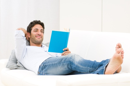 lying on couch: Smiling relaxed man reading a book lying on sofa Stock Photo