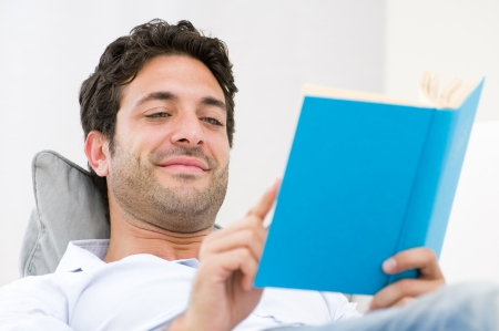 book reading: Smiling young man reading a novel book while relaxing on sofa