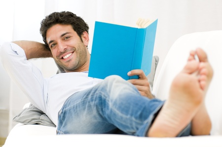 Smiling young man reading a book and relaxing on sofa at home photo