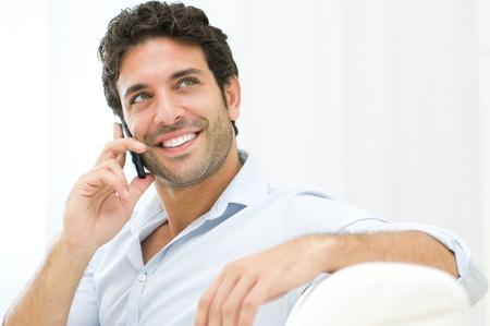 uomo felice: L'uomo giovane e sano sorridendo e parlando al telefono intelligente di casa