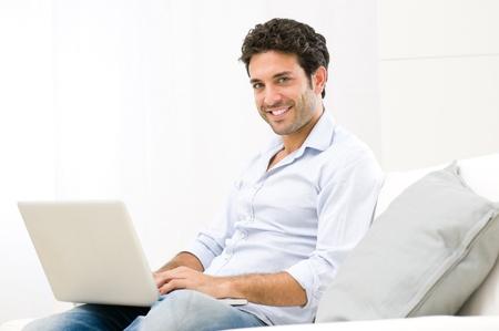 business man laptop: Feliz el hombre joven y sonriente trabajando en equipo port�til en casa