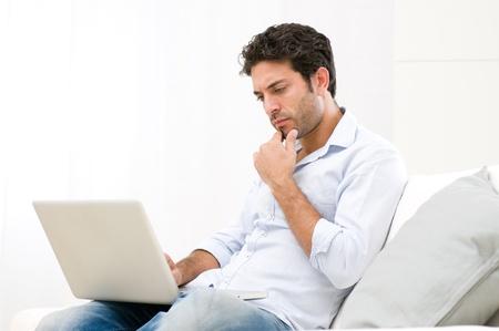 computer problems: Preoccupato giovane guardando il suo computer portatile con espressione pensosa Archivio Fotografico