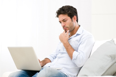 Worried young man looking at his laptop computer with pensive expression photo