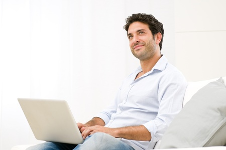 Smiling dreaming young man looking up while working at laptop computer Stock Photo