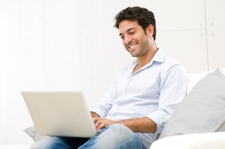 computadora: Feliz el hombre joven y sonriente mirando y trabajando en una computadora portátil en casa Foto de archivo