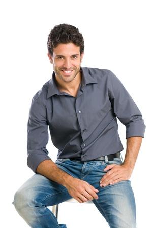 hombres jovenes: Joven satisfecho y orgulloso sentado en la silla y mirando a la cámara sobre fondo blanco