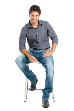 Trots en tevreden jonge man zitten op de stoel en kijken naar camera geà ¯ soleerd op witte achtergrond