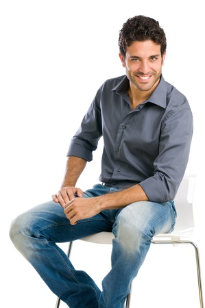 man in chair: Happy and proud young man sitting and looking at camera isolated on white background