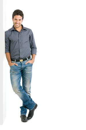 leaning: Happy smiling young man leaning against white wall with copy space an the right Stock Photo