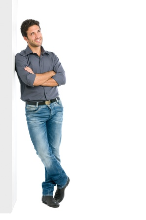 Happy smiling young man leaning against white wall with dreaming and pensive expression, copy space on the right photo