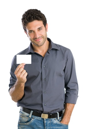 exhibiting: Satisfied young beautiful man holding and showing blank card ready for your text