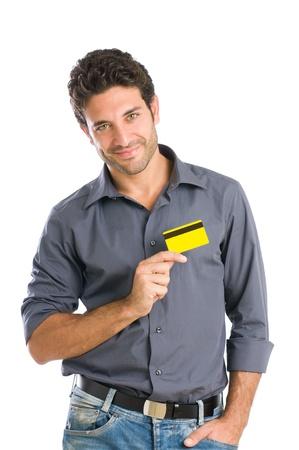 tarjeta de credito: Feliz el hombre joven que sostiene una tarjeta de cr�dito en el coraz�n aislado sobre fondo blanco