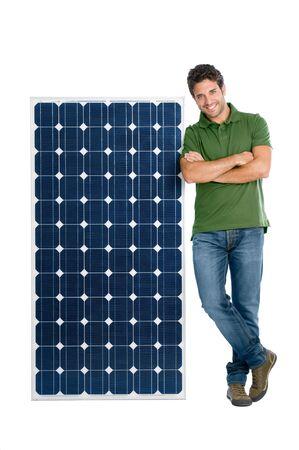 young man standing: Felice l'uomo sorridente in piedi con un pannello solare per l'energia rinnovabile, isolato su sfondo bianco