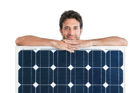 Smiling man showing and holding a solar panel isolated on white background photo