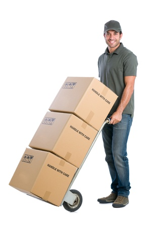 Smiling young delivery man moving boxes with dolly, isolated on white background photo