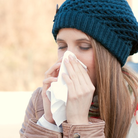 Pretty young woman blowing her nose with a tissue outdoor in winter Stock Photo - 11742949