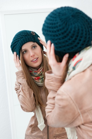 fitting room: Young beautiful lady trying winter clothes in front of a mirror