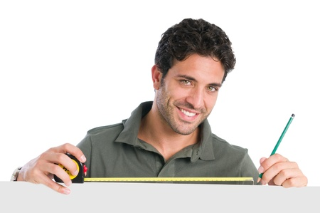Smiling worker man measuring with tape above a blank placard ready for your text photo