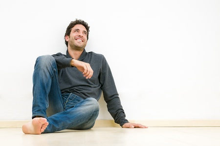 sitting on floor: Happy smiling man looking up and dreaming at his future Stock Photo