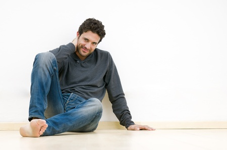 Happy satisfied young man looking at camera while sitting on floor Stock Photo - 12155602