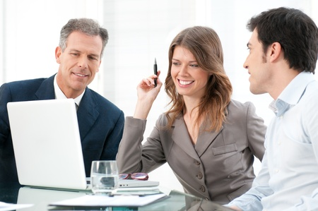 Smiling business team working together at laptop computer in the office Stock Photo - 12155609