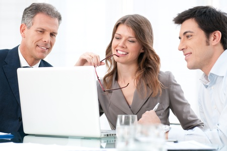Happy businesswoman looking at coputer with her business colleagues at office Stock Photo - 12155604