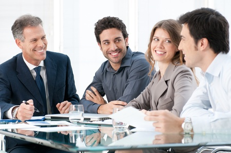 Happy smiling business people discussing and working together at office Stock Photo