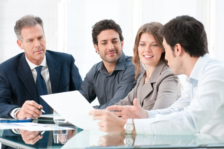 dedicated: Dedicated business people discussing together thair strategy at office Stock Photo