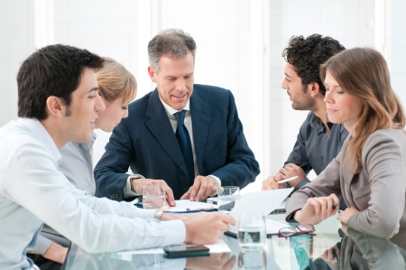 team working together: Mature businessman working and discussing with his colleagues at office