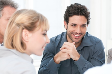 Smiling young business man working with his colleagues at office Stock Photo - 12155603