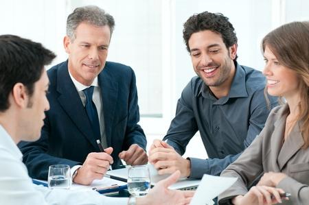 Glücklich Geschäftsleute diskutieren gemeinsam ihre Strategie bei Treffen im Amt Standard-Bild