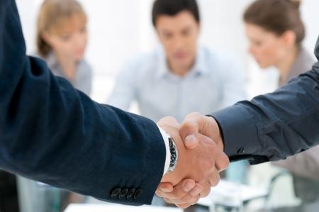 dandose la mano: Los hombres de negocios d�ndose la mano despu�s de un acuerdo durante una reuni�n Foto de archivo
