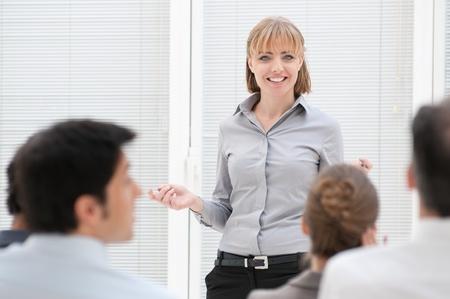 atender: Sonriente mujer ejecutiva discutir durante una presentaci�n de negocios