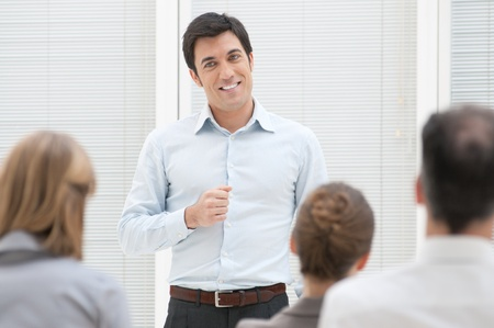 Smiling business man have a speech at business presentation  photo