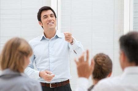 questionnement: Consultant en affaires r�pondant � une question lors d'une r�union au bureau Banque d'images