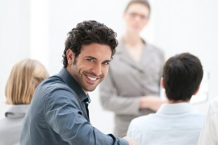 atender: Satisfecho de negocios mirando a la c�mara durante una conferencia de negocios