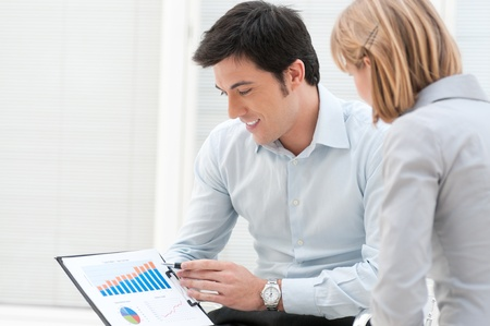dedication: Satisfied business man showing and pointing at growing chart with his colleague at office Stock Photo