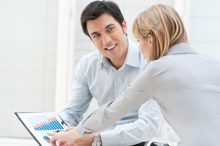 Happy businessman discuss with colleague on successful growing chart photo