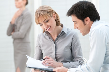 Business colleagues discussing on paperwork in a modern office photo