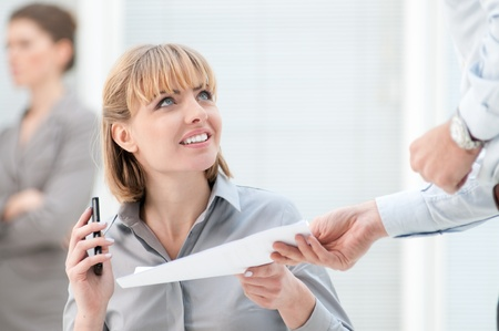 Smiling busy woman receive paperwork form a colleague at office Stock Photo