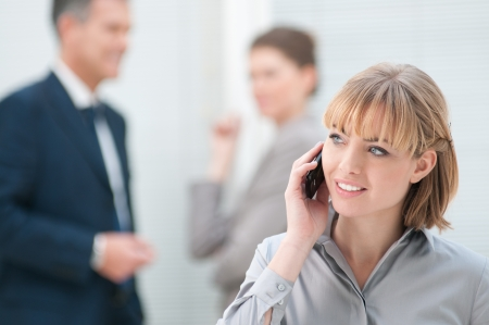 Smiling business woman talking on mobile phone at office photo