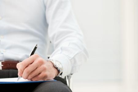 hombre escribiendo: Primer plano de la forma de escritura hombre de negocios en el portapapeles en la oficina Foto de archivo