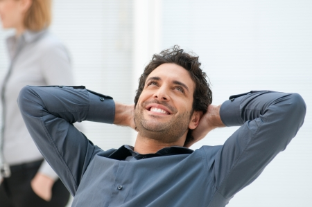 man resting: Happy smiling businessman looking up with dreaming expression at office