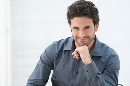 Satisfied proud business man looking at camera in the office with copy space photo